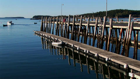 A boat leaves in the distance of a wooden dock near a... Stock Video Footage
