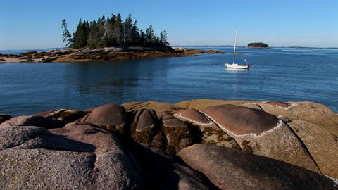 A sailboat is at anchor in a bay offshore a lobster village in Stonington, Maine Footage