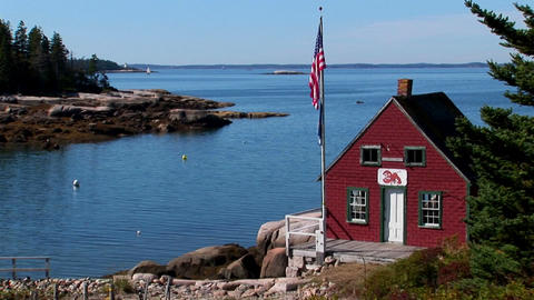 A red house sits on the edge of a bay at a lobster village in Stonington, Maine Footage