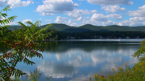 A glassy rural lake in Central Vermont is surrounded by trees and a cloudy blue sky Footage
