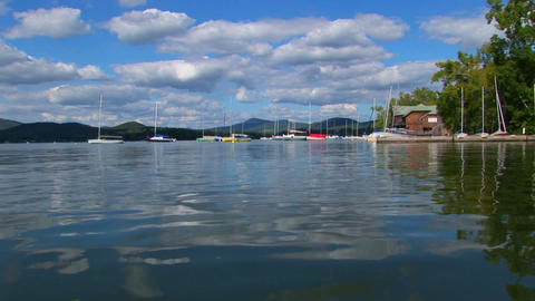 A cloudy blue sky and sailboats are seen in the distance of a glassy rural lake in Central Vermont Footage