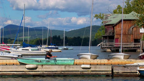 A man drifts in a rowboat near sailboats on a rural lake in Central Vermont Footage