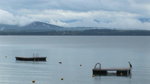 Clouds cover a mountain range in the distance of diving platforms on calm water at Lake Champlain in Footage