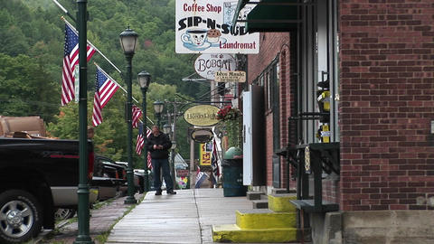 People walk into small downtown stores in Vermont Stock Video Footage