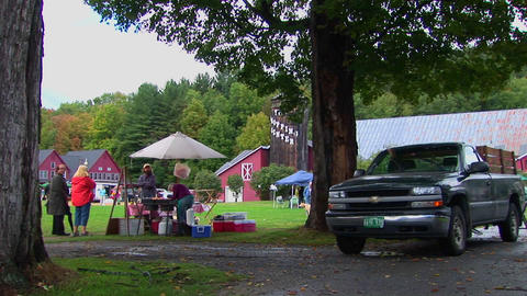 Families picnic near trees and red barns at a Country... Stock Video Footage