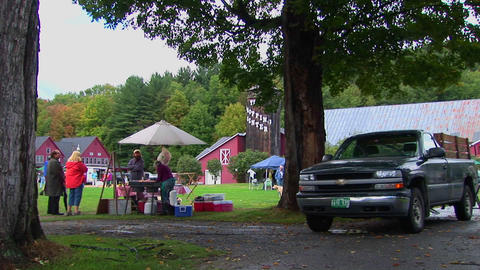 Families picnic near trees and red barns at a Country Fair in Vermont Footage