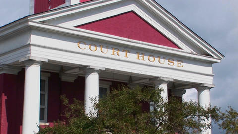 A gold sign marks a white and red building at a court... Stock Video Footage