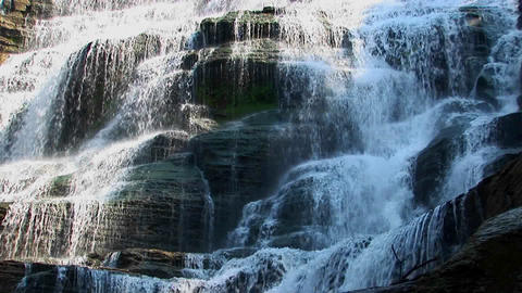 A wide waterfall flows over rock ledges in Ithaca Falls, New York Footage