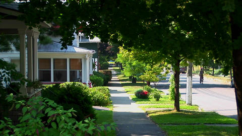 A tree covered pathway near houses on a street in small town America Footage