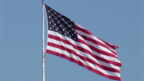 An American flag flies in the wind at day Stock Video Footage