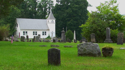 Gravestones stand in an old New England graveyard near a white church Footage