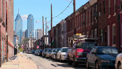 Vehicles are parked along a street of brick buildings in... Stock Video Footage