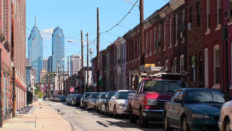 Vehicles are parked along a street of brick buildings in Philadelphia, Pennsylvania Footage