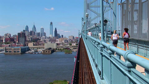 A group of joggers run across the Ben Franklin Bridge... Stock Video Footage