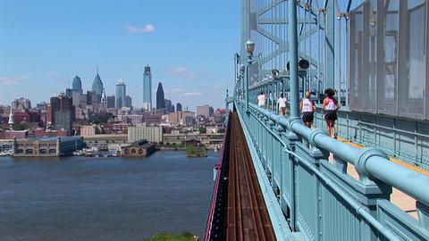 A group of joggers run across the Ben Franklin Bridge... Stock Video Footage