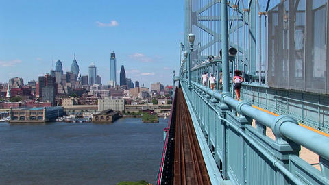 A group of joggers run across the Ben Franklin Bridge leading to Philadelphia, Pennsylvania Footage