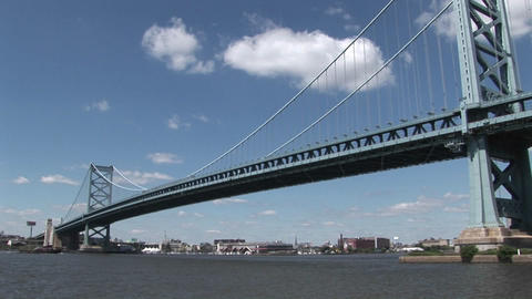 A boat passes under the Ben Franklin Bridge which leads... Stock Video Footage