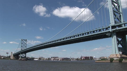 A boat passes under the Ben Franklin Bridge which leads to Philadelphia, Pennsylvania at day Footage