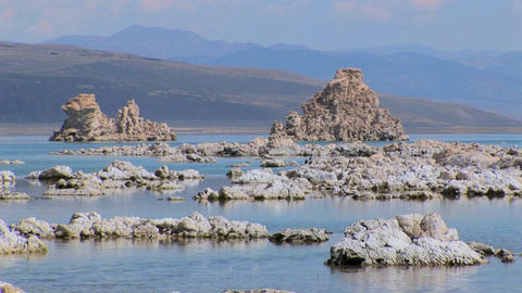 Clouds are above tufa formations sitting in water while mountains overlap in the distance at Mono La Footage