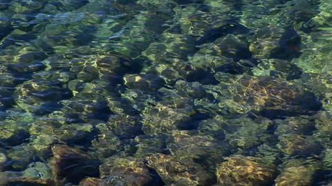 Ripples of water in Lake Tahoe distort the view of rocks below the surface of the Sierra Nevada moun Footage