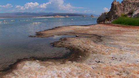 A multi-colored shore with clouds above rocks sitting in... Stock Video Footage