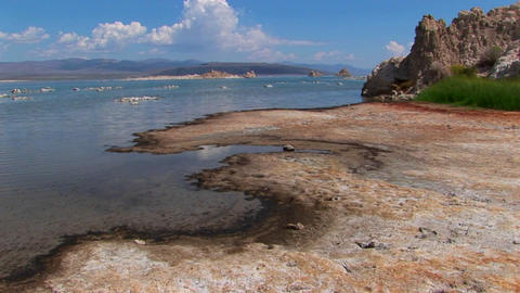 A multi-colored shore with clouds above rocks sitting in water while mountains overlap in the distan Footage
