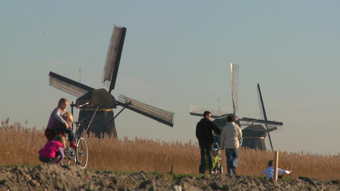 Dutch citizens walk on a footpath in front of windmills Stock Video Footage