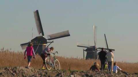 Dutch citizens walk on a footpath in front of windmills Footage