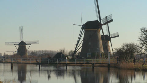 Dutch citizens walk on a bridge in front of windmills Footage