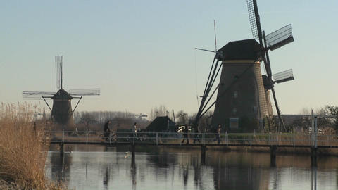 Dutch citizens cross a footbridge in front of windmills along a canal in Holland Footage