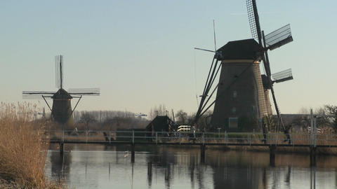 Dutch citizens cross a footbridge in front of windmills... Stock Video Footage