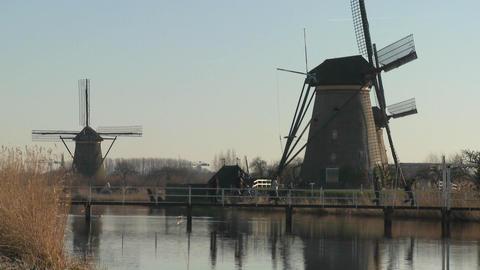 Dutch citizens cross a footbridge in front of windmills... Stock Video Footage