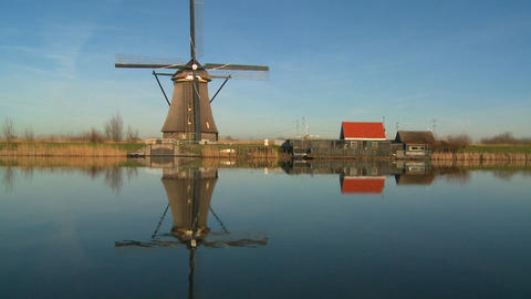 A windmill stands proudly along a canal in Holland Stock Video Footage