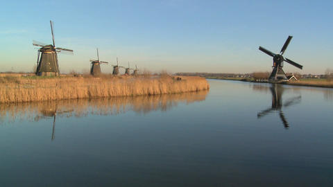 Windmills line a canal in Holland Stock Video Footage