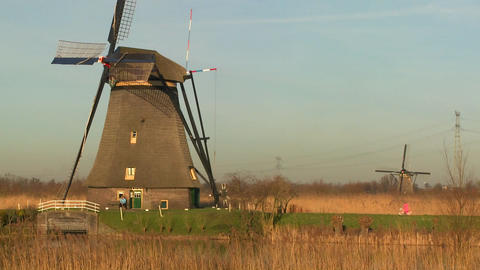 A woman rides a bicycle past a windmill in Holland Footage
