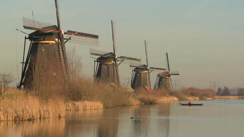 Windmills line up perfectly along a canal as a small boat crosses in the distance Footage