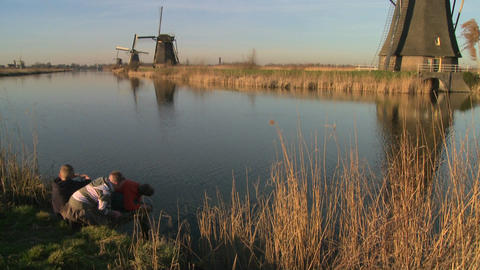Children play in front of windmills along a canal in Holland Stock Video Footage