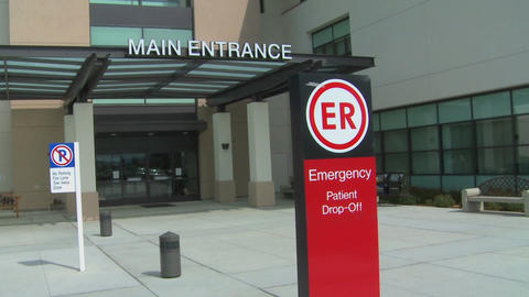Pan from a hospital facade to an emergency room entrance Stock Video Footage