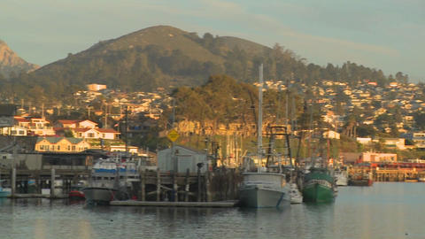 A pan across the small Central California town of Morro Bay with fishing boats in the harbor Footage