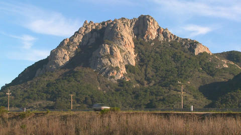 A mountain rises along a busy highway near Morro Bay, California Footage
