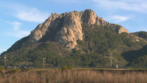 A mountain rises along a busy highway near Morro Bay,... Stock Video Footage