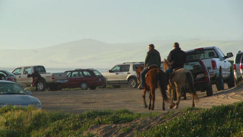 People ride horses along a beachside parking lot in... Stock Video Footage