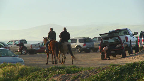 People ride horses along a beachside parking lot in California Footage