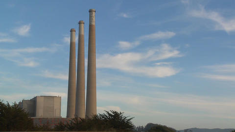 A time lapse shot of clouds moving behind the smokestacks of a power plant Footage