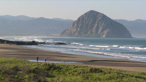 An establishing shot of a large rock along the coast of California near Morro Bay Footage