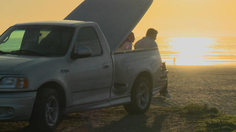 A couple sits on the flatbed of a pickup truck in this... Stock Video Footage