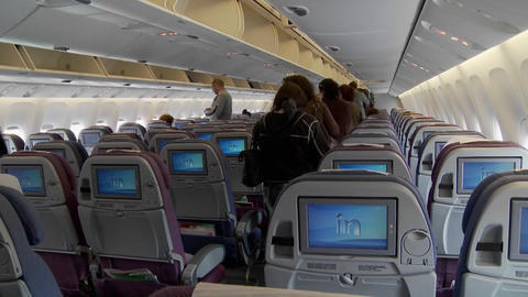 The interior of a modern airplane with passengers boarding Footage