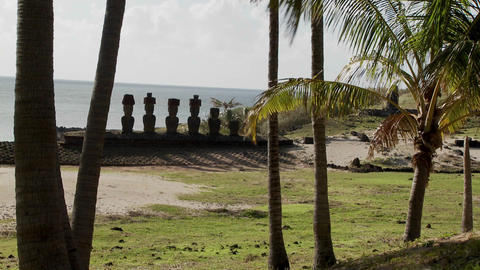 Easter Island statues stand in a long row on a distant beach Stock Video Footage