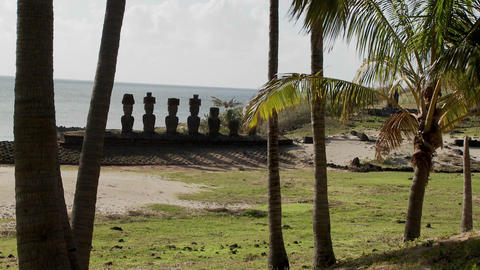 Easter Island statues stand in a long row on a distant beach Footage