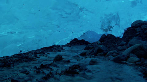 An underground river flows beneath an ice cave Footage